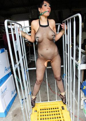 Restrained brunette in a crotchless bodystocking has her nipples clamped