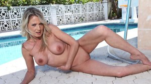 Mature lady Bridgette Lee takes off her bikini under an umbrella by the pool