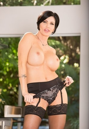 Brunette MILF Shay Fox strips to black stockings and garters