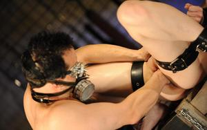 Restrained blonde female has her pussy worked over by man in gas mask