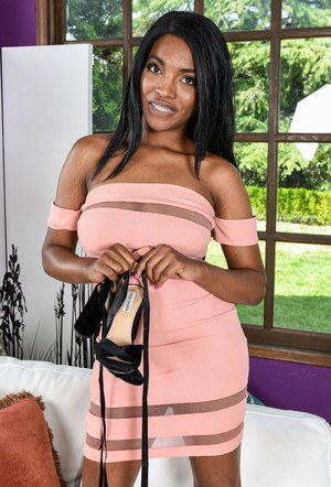 Ebony pornstar Daya Knight removes her dress to pose naked on a couch