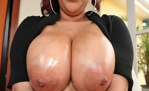 Redhead BBW seduces and tit fucks her guy with her oiled up boobs