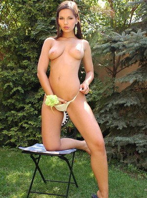 Solo model Eve Angel uncovers her firm tits as she undresses in backyard