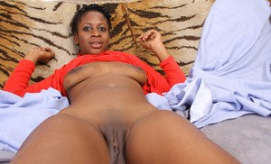 Ebony solo model with short hair hikes up her dress to expose her pink pussy