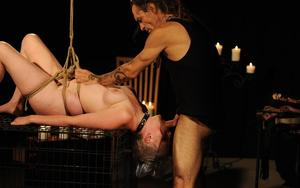 Older woman is suspended by ropes and forced to perform oral sex