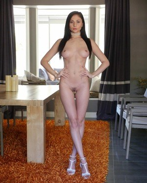 Sexy female with dark hair crosses her legs while posing in the nude