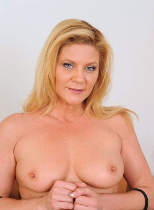 Mature lady Ginger Lynn strips to her tan colored stockings to masturbate