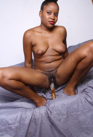 Black female works her pink snatch over with a sex toy while posing naked