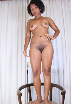 Black amateur slips off retro styled lingerie to model naked on a chair