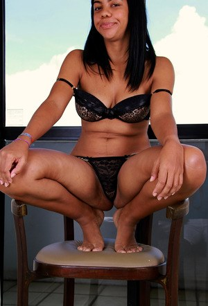 Black female showcases her bald pussy on a chair after bra and panty removal