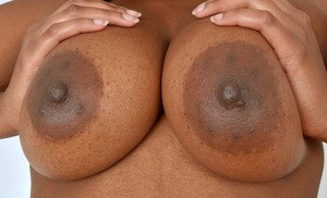 Black amateur Monique Symone holds her big tits as she goes about getting nude