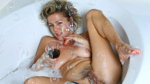 Mature lady soaks in a bathtub while toying her hairy pussy
