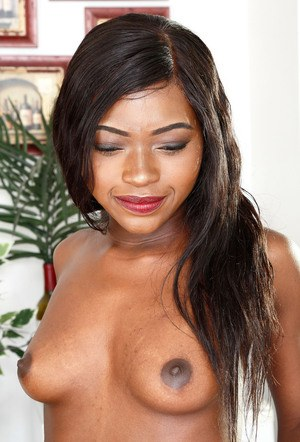 Black girl bares her small tits as she undresses for nude poses