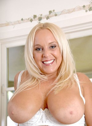 Older blonde chick Alexis Golden exposes her huge boobs in the kitchen