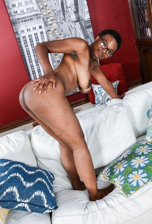 Ebony chick with short hair and glasses makes her nude modeling debut