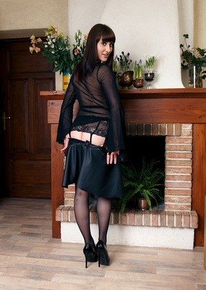 Amateur model in a see thru shirt strips to black stockings by fireplace
