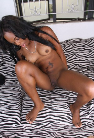 Naked amateur model parts the labia lips of her bald black pussy