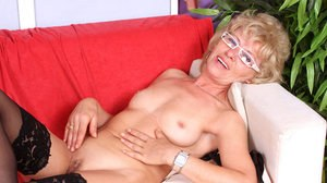 Older lady in funky glasses strips to black stockings before finger fucking