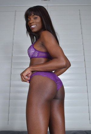 Black solo model Ana Foxxx works free of purple lingerie to pose naked