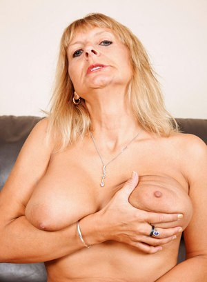Older woman exposes her nice melons as she undresses on a leather couch