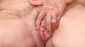 Horny granny removes her dress and lingerie to toy her pussy