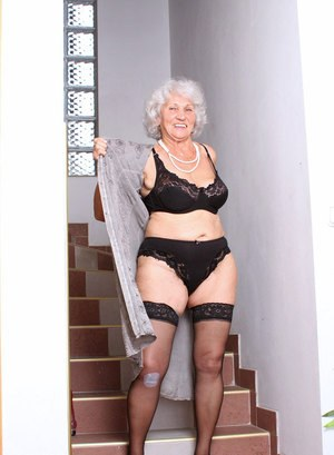 Aged lady removes her long dress and black lingerie prior to toying her pussy