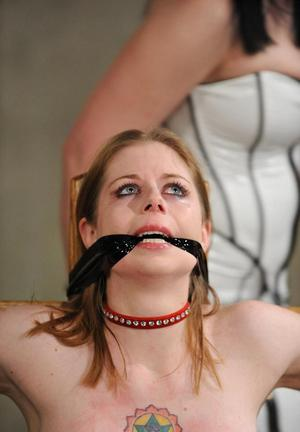 Restrained chick in black stockings being tortured by another woman