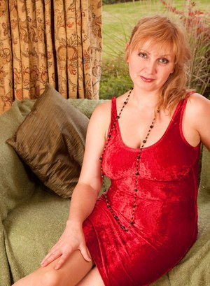 Older woman doffs her red velvet dress to pose naked in tan colored stockings