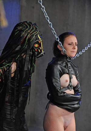 Captive girl is masturbated while restrained with a straight jacket and chains
