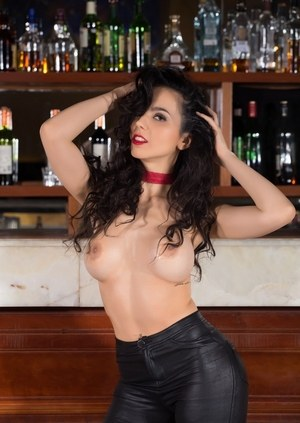 Dark haired female Flavia De Celis strips to mesh stockings on a bar