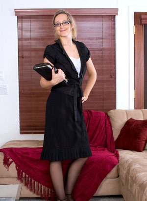 Mature MILF Nicole Logan strips down to black stockings with her glasses on