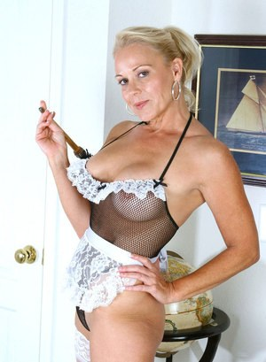 Older blonde woman struts about the house in revealing maid outfit