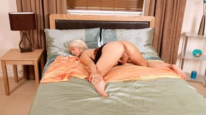 Older lady with a bob cut and big tits plunges her fingers into her pussy