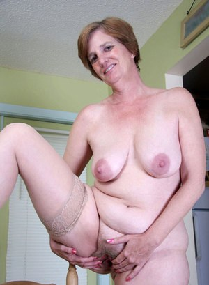 Mature redhead woman shows off her fat body and saggy boobs as she undresses