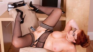 Thick mature redhead sticks a sex toy up her twat wearing glasses and nylons
