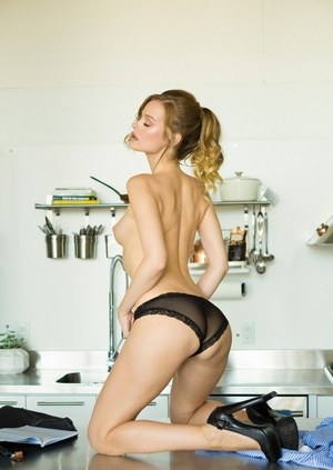 Solo girl Olivia Preston poses in a pair of high heels only on kitchen counter