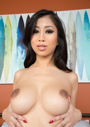 Asian solo model Jade Kush frees her big boobs from her bra on top of bed