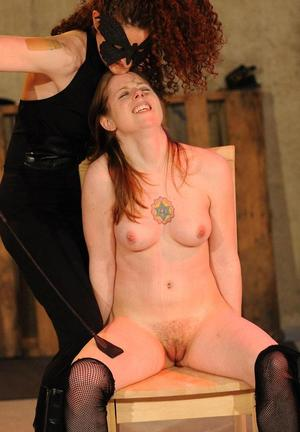 Tattooed female is forcefully masturbated by a clothed woman in a dungeon