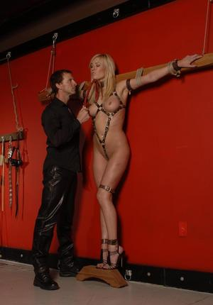 Submissive blonde female is tied to a wall and used as her Master sees fit