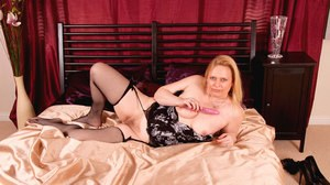 Older lady in black mesh stockings pleasures her pussy with a vibrator