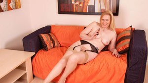 Chubby blonde female strips down to tan nylons and garters before masturbating