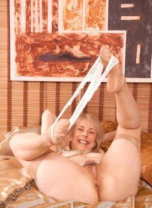 Mature woman pleasures her twat with Ben Wa balls wearing tan nylons