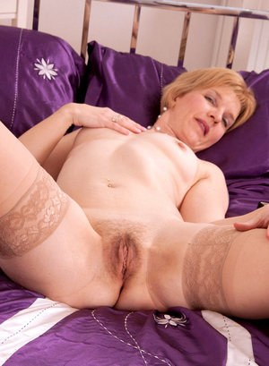 Older lady pleasures her hairy snatch after stripping to tan nylons