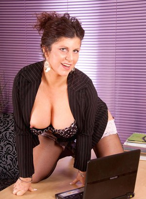 Mature lady shows off her twat in her home office in sexy stockings