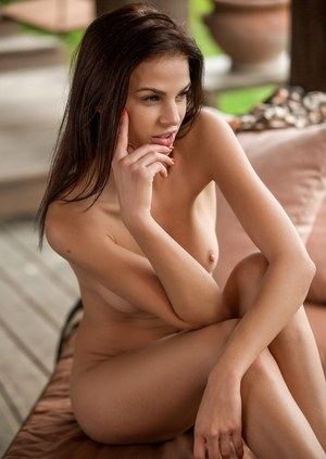 Centerfold model uncovers her nice tots as she gets naked on a lounge chair