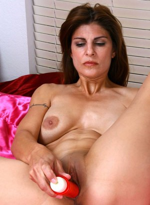 Mature woman Monique sticks a sex toy up her pink pussy atop her bed