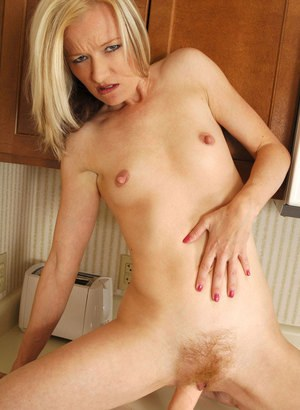 Natural blonde chick Heidi Hanson inserts a dildo into her cunt in the kitchen