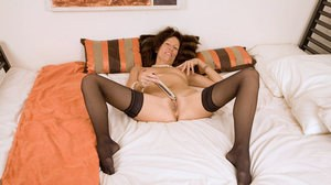 Classy older lady strips to her black stockings before masturbating