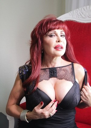 Older redhead cups a big tits after stripping to black stockings and garters