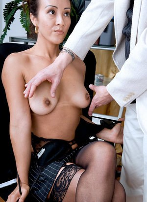 Older woman seduces a younger man in her office attired in black stockings